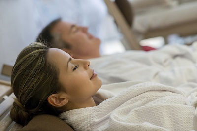 Happy couple relaxing at the spa in a romantic getaway